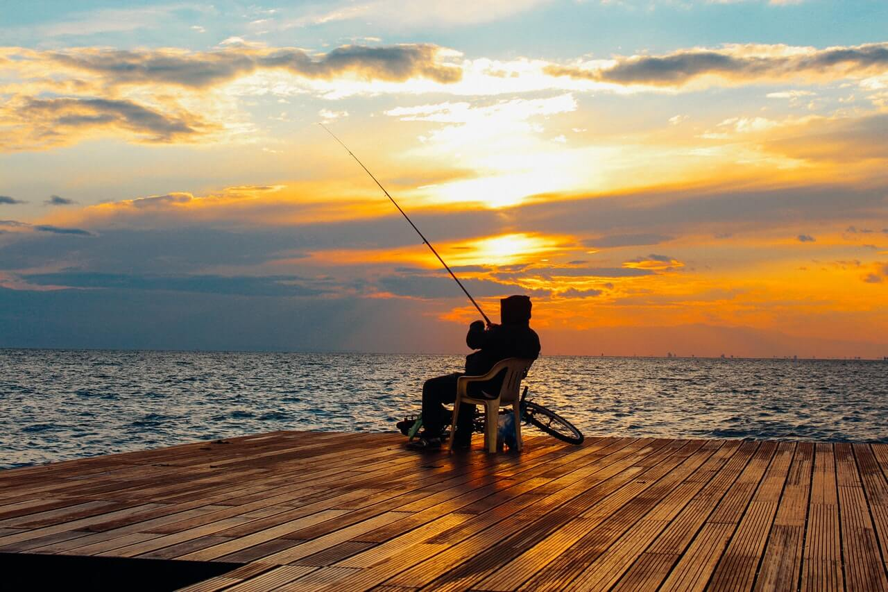 person sitting on chair holding fishing rod