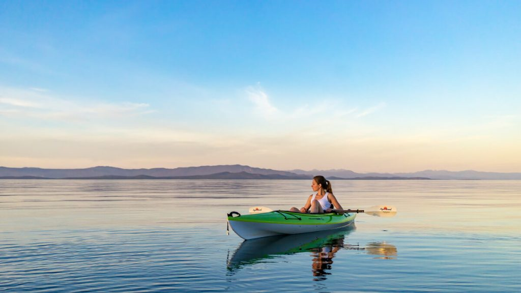 woman on green and white kayak holding yellow oar