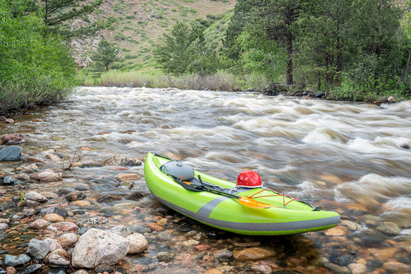 inflatable whitewater kayak on a shore of a mountain river