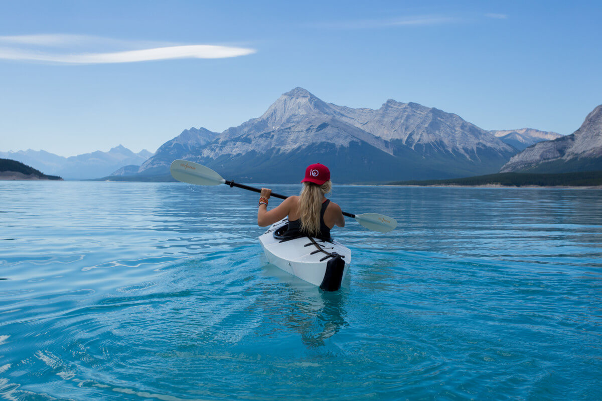 woman riding on white kayak facing mountain alps