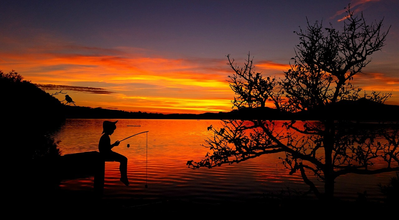 child fishing in lake