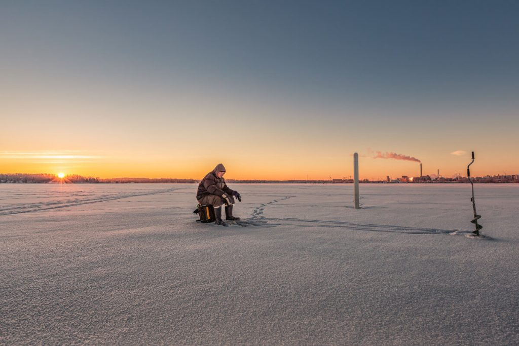 fisherman sitting on stool on ice field