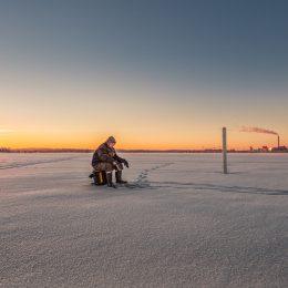 fisherman sitting on stool on ice field