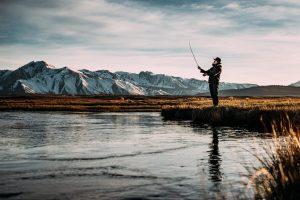 man fishing on river near mountain alps