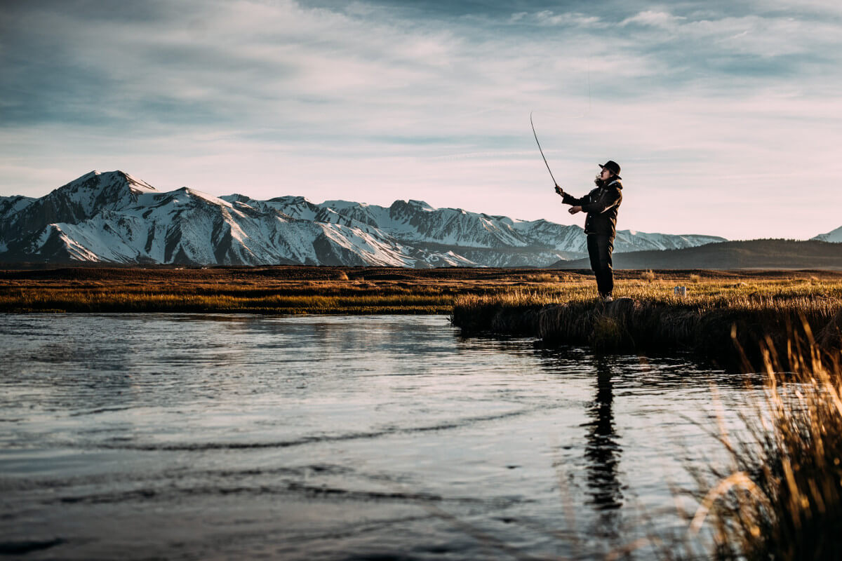 man fishing on river near mountain alps