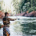 man fly fishing during daytime in river