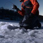 man ice fishing on a lake in winter
