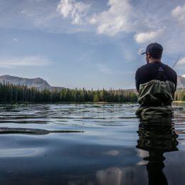 man wearing wader and fishing in lake