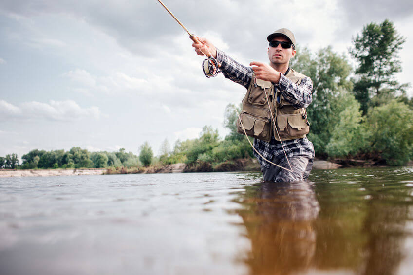 fisherman is throwing spoon of fly rod in water