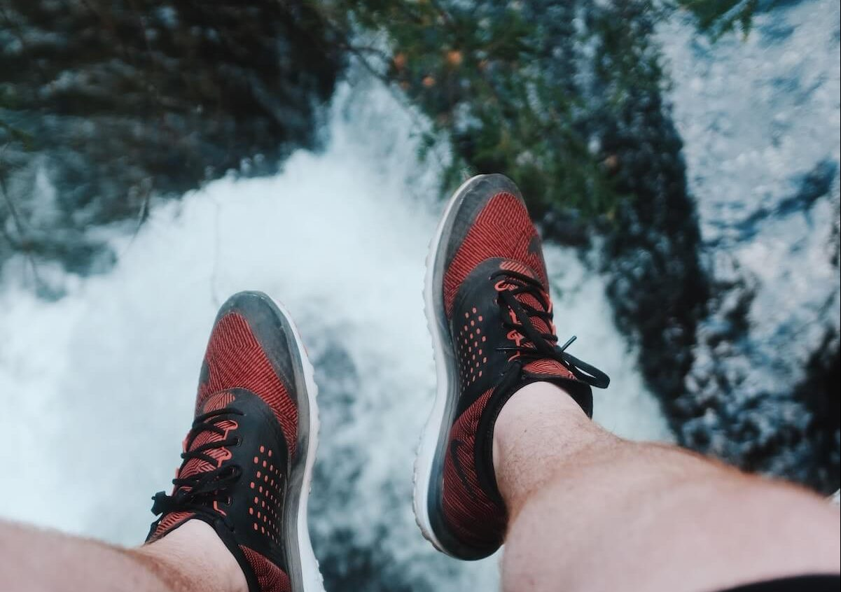 man feet over waterfall