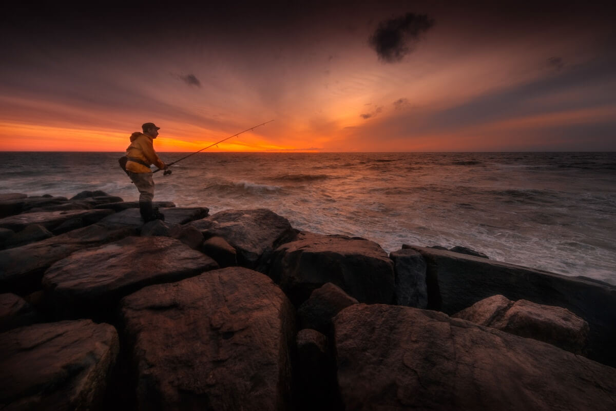 man fishing in sea in sunset