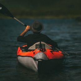 man in kayak by mountains