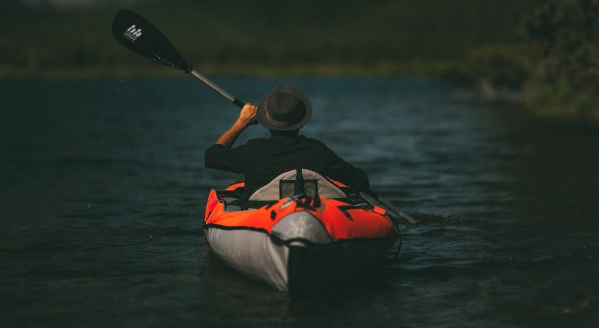 man in kayak by mountains
