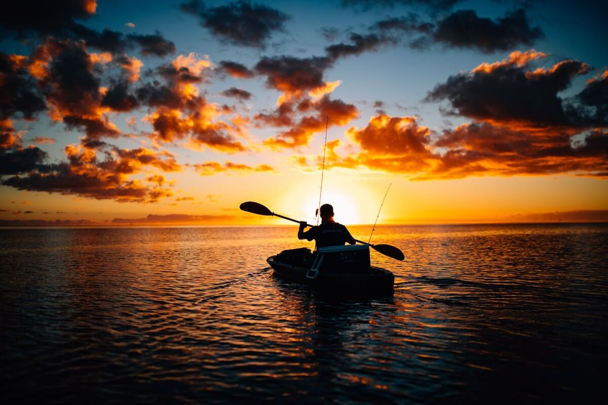 man kayak fishing in sunset