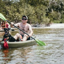man padlling a kayak with dog in it