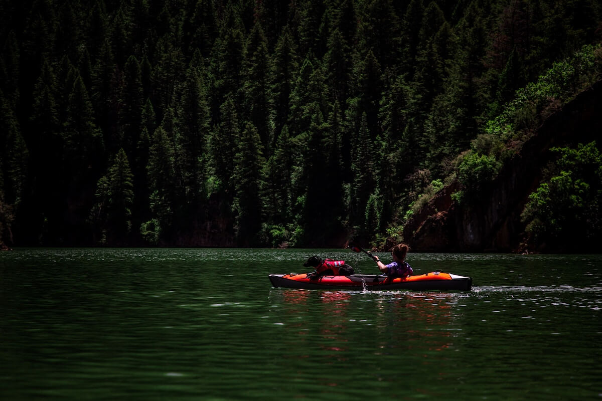 women and dog in kayak