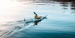 man in a blue kayak on lake