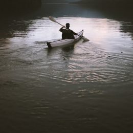 person in white kayak in lake