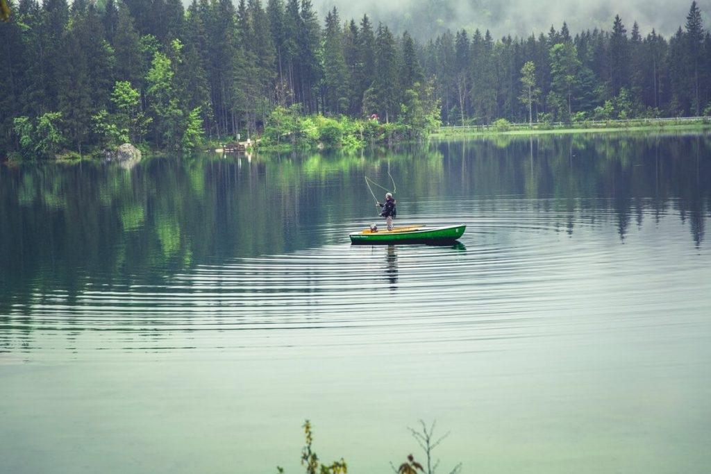 person on boat fishing in lake