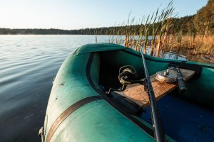 inflatable fishing boat on the lake at sunrise