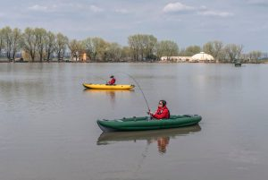 two fisherwomen on inflateble kayaks with fishing tackle