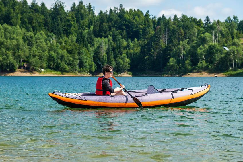 woman kayaking in inflatable tandem kayak on lake